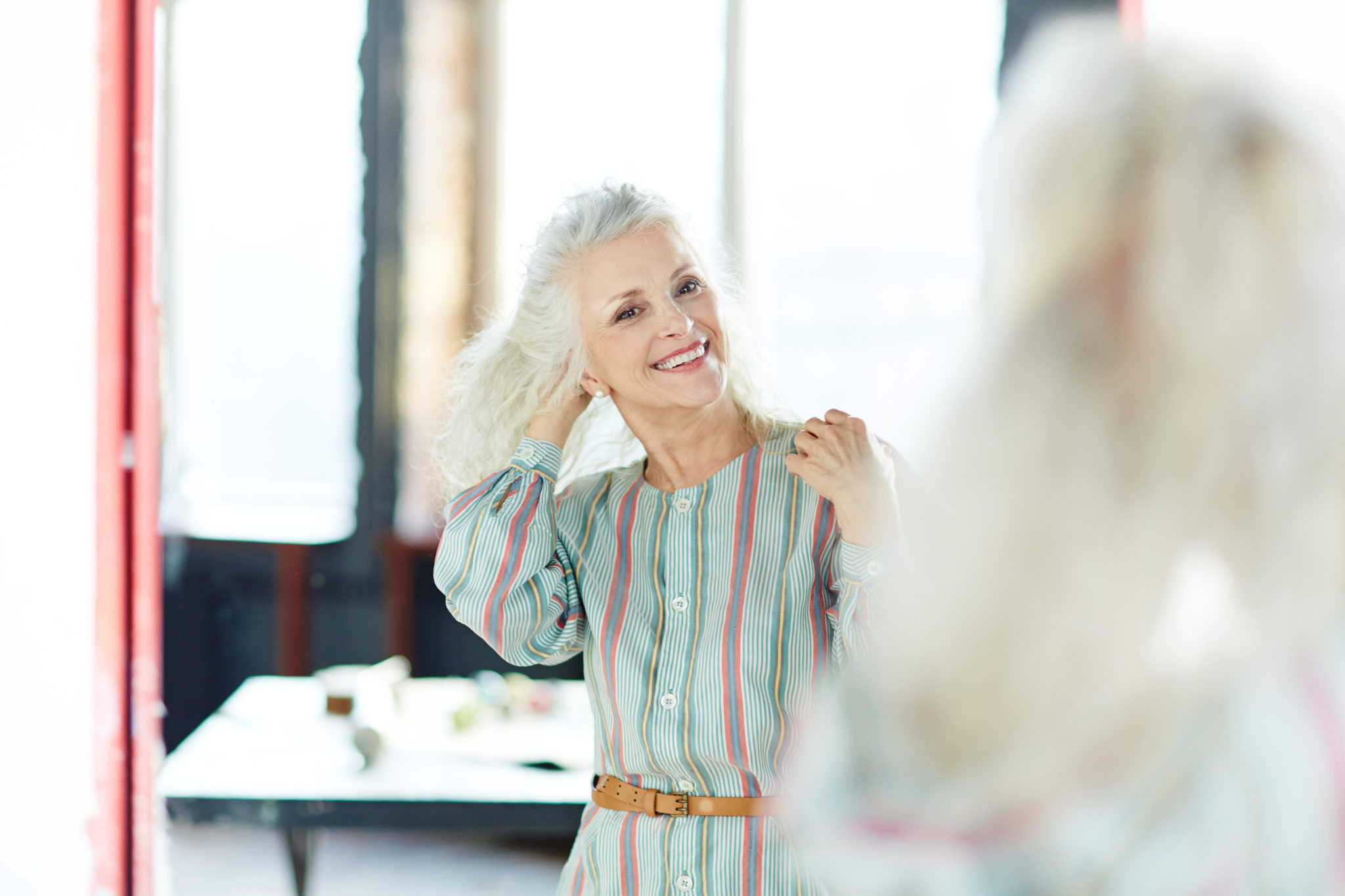 woman looks into mirror and smiles
