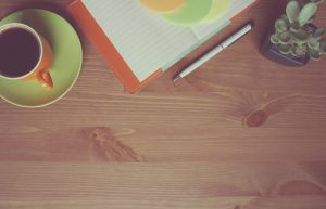 Coffee on table with paper and pen