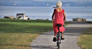 older woman riding bicycle towards sea