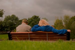 older man and woman sit on a bench with their backs towards the camera