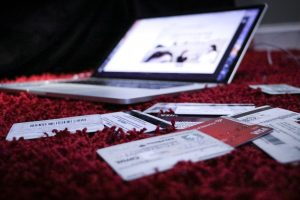 laptop sitting on blanket with credit cards around it