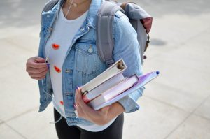 College student walking around campus with books