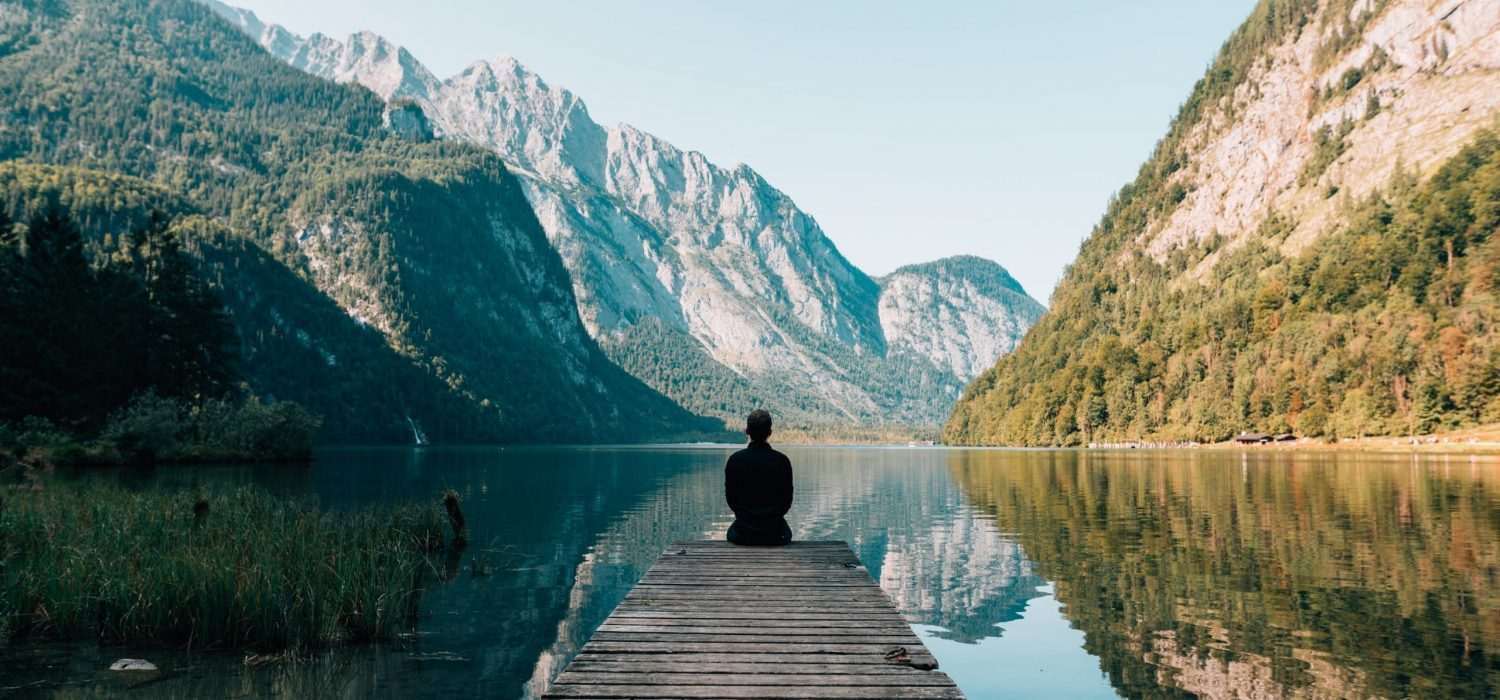 traveler sitting alone at the edge of a dock looking into nature