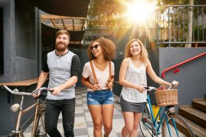 Three young adults walking together with bike
